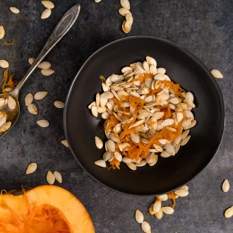 Black bowl with pumpkin seeds and pumpkin half face up